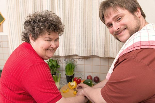 Two people washing their hands in a kitchen